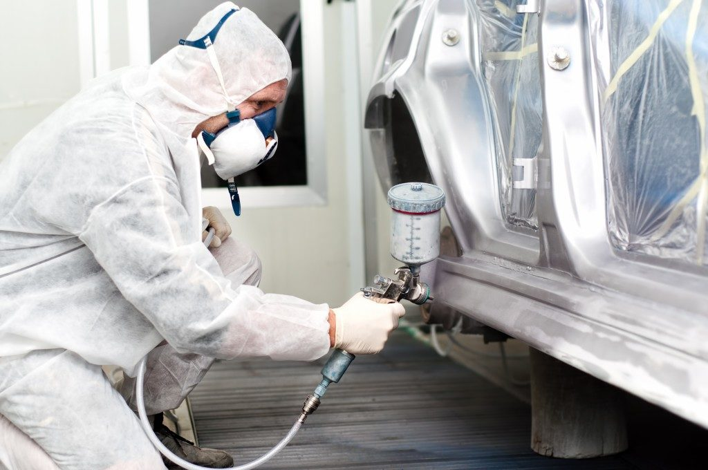 Car being painted by man