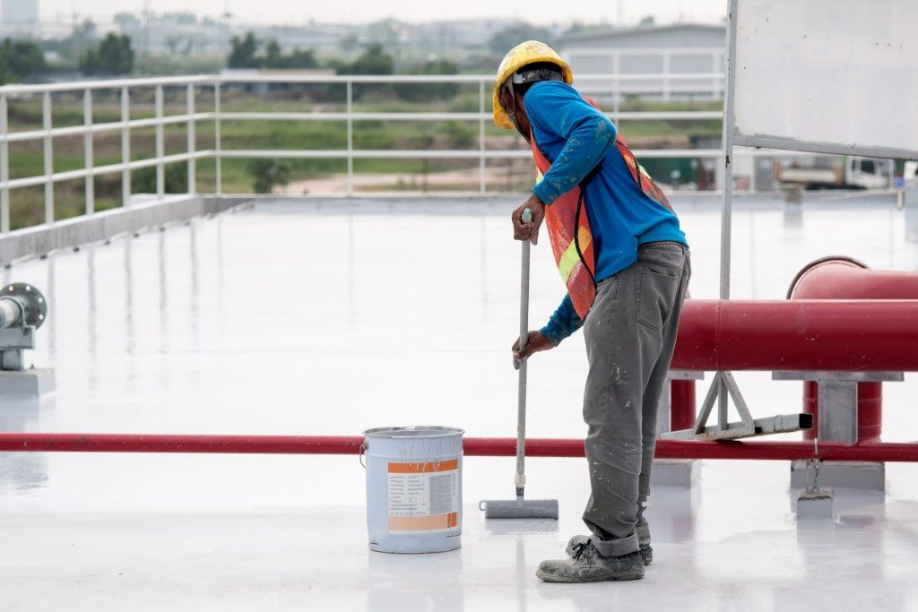 Man coating floor with paint