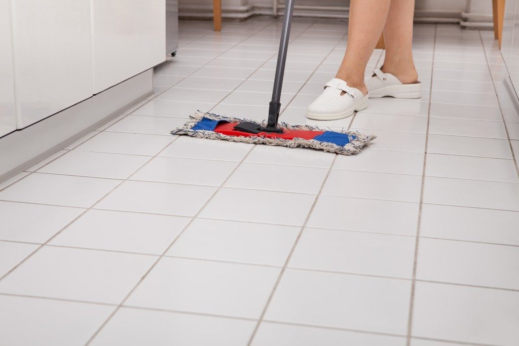 person cleaning tiles