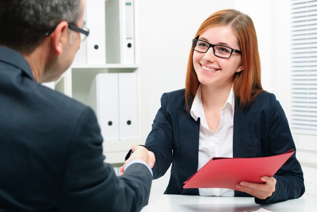 Woman shaking hands with a man while holding a red folder in a business environment