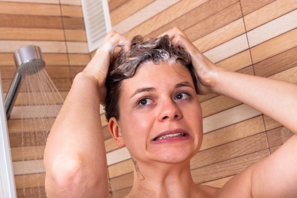 Woman showering to clean hair