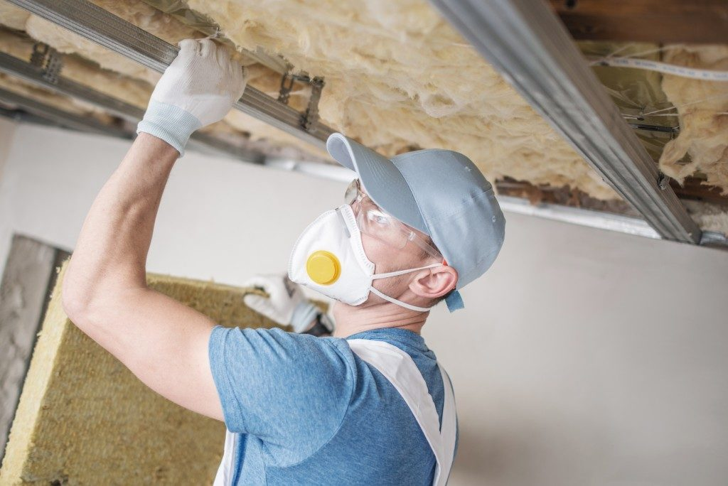 man installing insulation in the roof