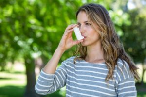 woman with asthma using an inhaler