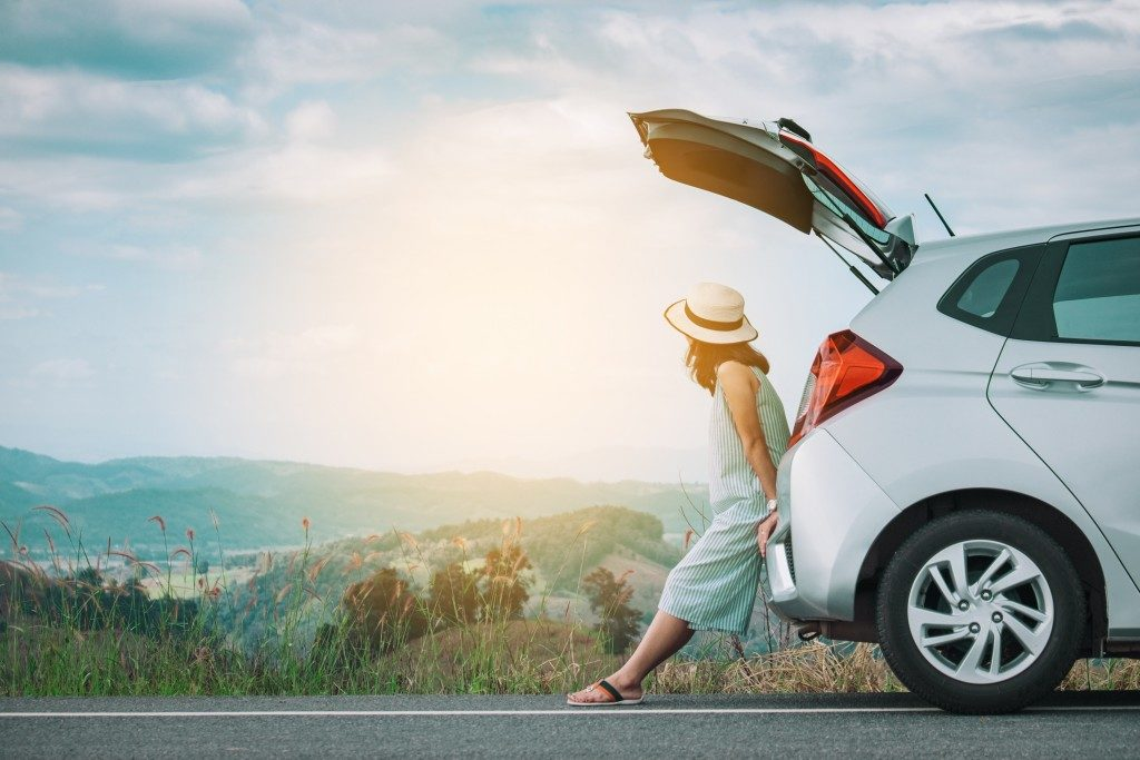 woman sitting at the trunk of her car
