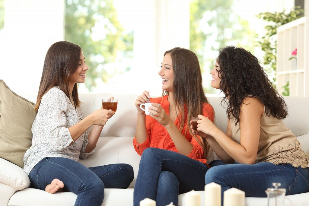 Friends having coffee and tea while chatting on the couch