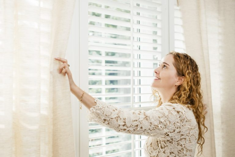 Woman looking out window with blinds