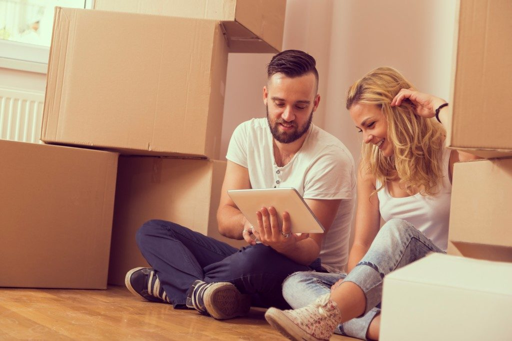 Young couple sitting on the floor with boxes surrounding them