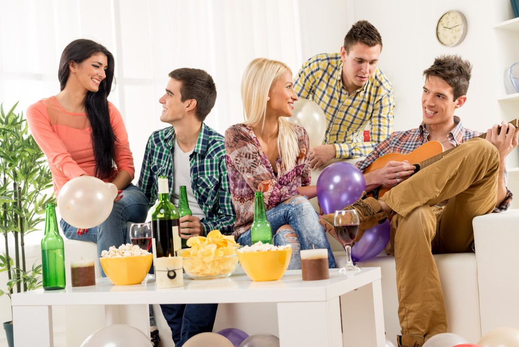 A small group of young people hang out at the house party,