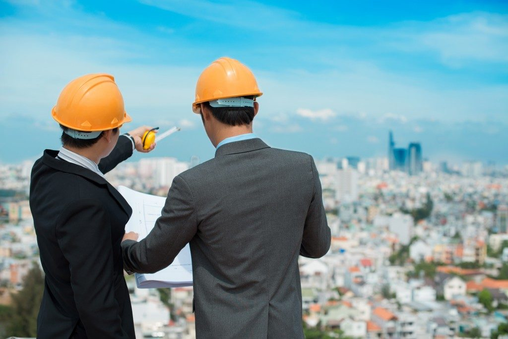 Businessmen in hardhats taking a look at the blueprint in urban environment