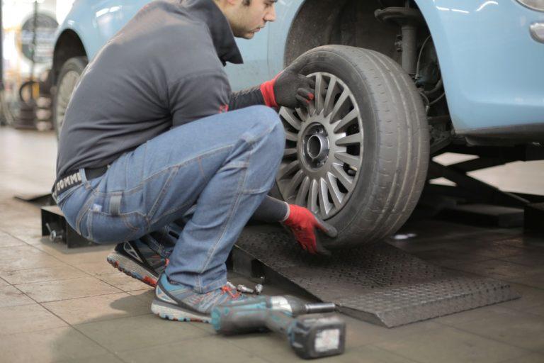 man fixing a car wheel