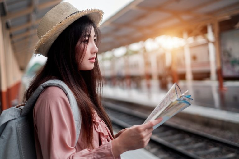 asian tourist waiting for train holding map