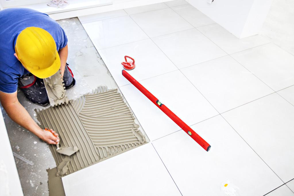 man installing bathroom tiles