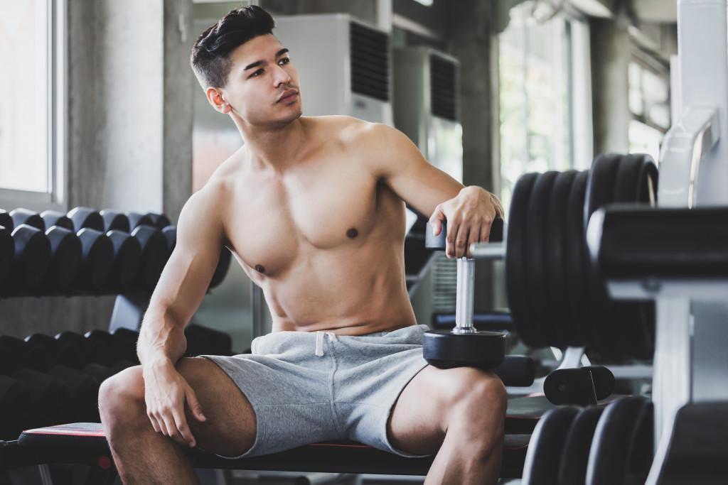 a guy sitting on a gym bench