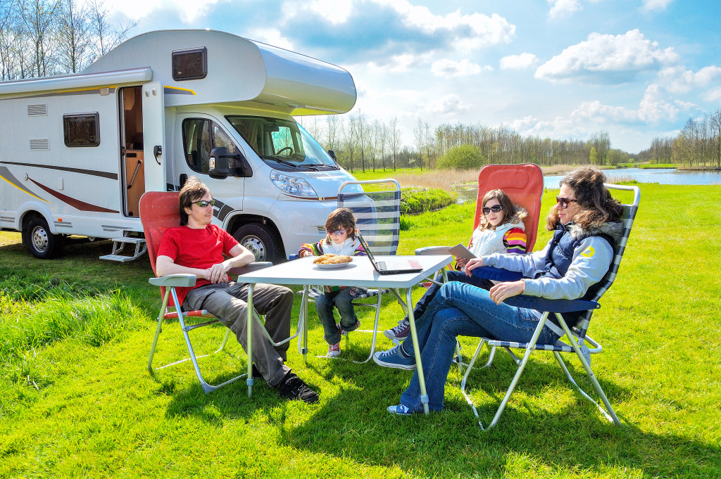 family relaxing together outdoors with their recreational vehicle